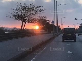通りを行く車と夕焼けの写真・画像素材[2744849]