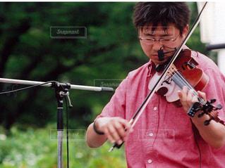 野外でバイオリンを演奏する男性の写真・画像素材[1091290]