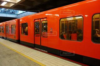フィンランドの駅で停止して長いオレンジ色の電車の写真・画像素材[1041020]