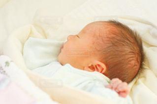 赤ちゃんがベッドの上で横になっています。の写真・画像素材[1040379]