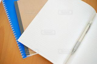 木製テーブルの上のノートとペンの写真・画像素材[1207450]