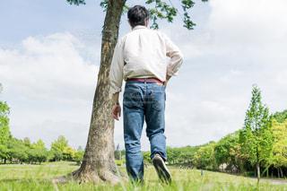 木の隣に立っている男の写真・画像素材[1281843]