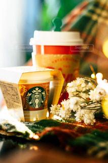 近くのコーヒー カップの横にあるテーブルの上に食べ物のアップの写真・画像素材[1674810]