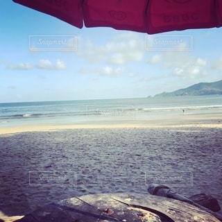 砂浜の上に座って傘の写真・画像素材[1041224]