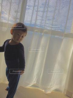 カーテンの前に立っている少年の写真・画像素材[1041256]