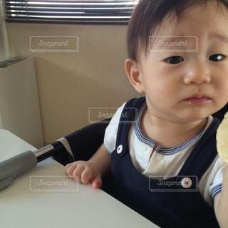 テーブルに座っている小さな子供の写真・画像素材[1046033]