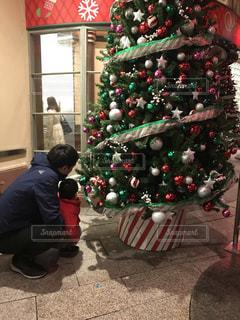 クリスマス ツリーの横に立っている人の写真・画像素材[1760633]