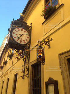 建物の側面からぶら下がっている時計の写真・画像素材[1041316]