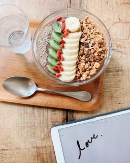 木製のテーブルの上に座っている食べ物のボウルの写真・画像素材[2440818]