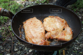 屋外でフライパンを使って焼く豚肉の写真・画像素材[1089221]