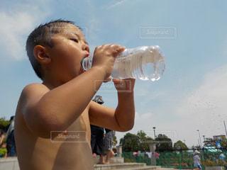 水遊びの合間、ミネラルウォーターをガブ飲みする4歳児。の写真・画像素材[1315368]