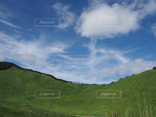 背景の山に大規模なグリーン フィールドの写真・画像素材[1262355]