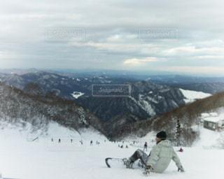 煙る山頂の雪の上にスキーに乗っている人のグループの写真・画像素材[1438208]