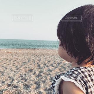 ビーチに座っている少女の写真・画像素材[1046875]
