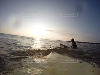 海でサーフボードで波に乗って男の写真・画像素材[1049833]