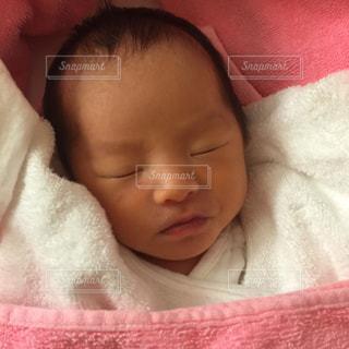 ピンクの毛布に包まれている赤ちゃんの写真・画像素材[1080744]