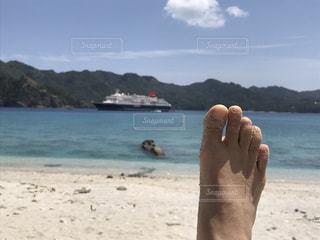 水の体の近くのビーチに立っている人の写真・画像素材[1119791]