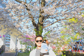 桜の木の前に立っている男と犬の写真・画像素材[1101616]