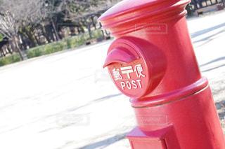 通りの側に座っている赤いポストの写真・画像素材[1049586]
