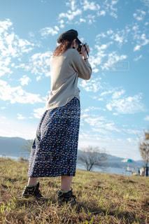 草原でカメラを構える女性の写真・画像素材[1576024]