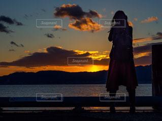 日没前に立ってカメラを構えている女性の後ろ姿の写真・画像素材[1740598]