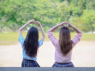 手でハートを作る女子高生の後ろ姿の写真・画像素材[2117190]