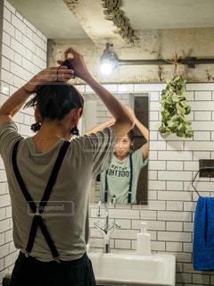 鏡の前で髪をくくる女性の写真・画像素材[2189021]