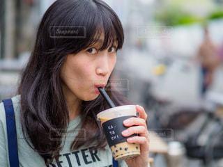 カメラ目線でタピオカドリンクを飲む女性の写真・画像素材[2189075]