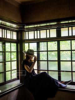 窓際に座る麦わら帽子の女性の写真・画像素材[2282492]