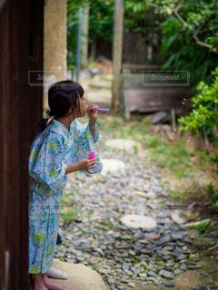 実家の庭でシャボン玉を楽しむ浴衣姿の女の子の写真・画像素材[2282495]