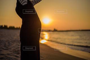 浜辺で、日没の前に立っている人の写真・画像素材[1229483]