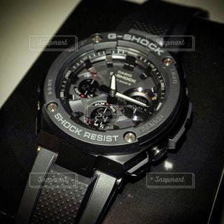 テーブルの上の黒い時計の写真・画像素材[1050816]