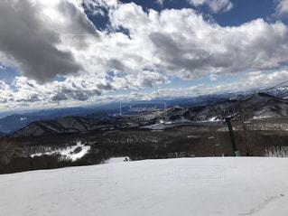 雪に覆われた斜面に立っている人の写真・画像素材[1051391]