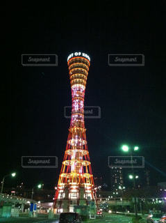 神戸ポートタワーをバック グラウンドで夜ライトアップ時計塔の写真・画像素材[1051781]