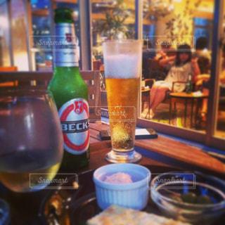 ボトルとテーブルの上のビールのグラスの写真・画像素材[1051711]