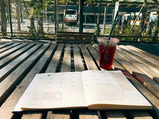 テラス席の木のテーブルに広げられた手帳の4月のページの写真・画像素材[1052761]