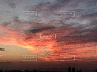 夕焼け空に浮かぶ雲のグループの写真・画像素材[1053704]