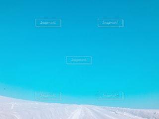 雪の上に空気を通って飛んで男覆われた斜面の写真・画像素材[1056066]