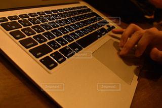 テーブルの上に座っているラップトップ コンピューターを使用している人の写真・画像素材[1456604]