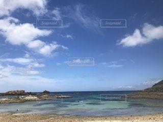 水の体の横にある砂浜のビーチの写真・画像素材[1429708]