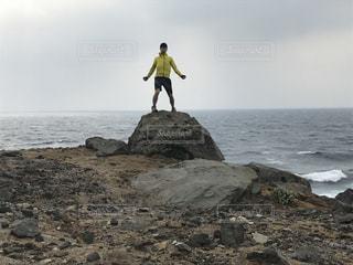 海の横にある岩のビーチに立っている人の写真・画像素材[1057363]