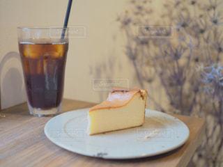 コーヒー カップの横にある皿の上のケーキの一部の写真・画像素材[1510005]