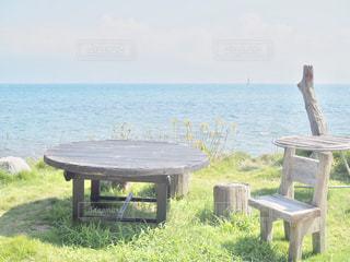 水の体の横にあるピクニック用のテーブルの写真・画像素材[1537981]