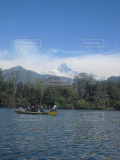 背景の山と水の体中の小型船の写真・画像素材[1063174]