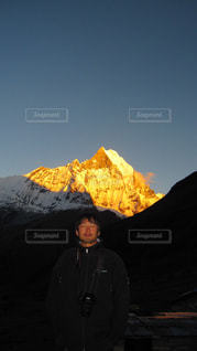 山の前に立っている男の写真・画像素材[1063237]