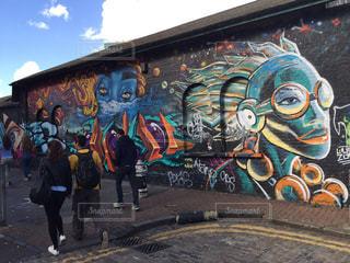 覆われている落書きの壁の横に立っている人々 のグループの写真・画像素材[1064324]