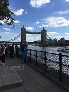 水の体の上に橋の上歩く人のグループの写真・画像素材[1067104]