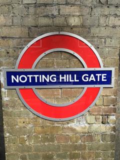 れんが造りのバック グラウンドでロンドンの地下鉄の建物の前にある看板の写真・画像素材[1067107]