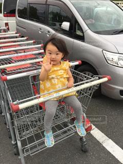 駐車場で座っている女の子の写真・画像素材[1067792]