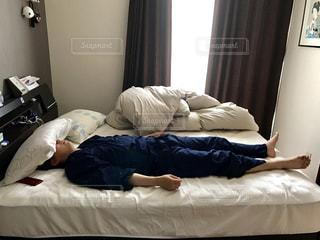 ベッドの上で横になっている人の写真・画像素材[1152835]